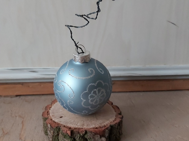 blauwe kerstbal op houten plankje